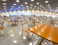Fast food interior concept a large hall in metallic style illuminated by lot of lamps and filed by furniture tables seats and Stock Photo