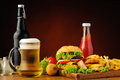 Fast food menu and beer with hamburger chicken nuggets french fries Royalty Free Stock Photo