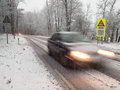 Fast moving car brakes in a snow storm as it passes warning sign under morning light motion blur is used to emphasise speed Royalty Free Stock Photo