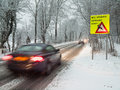 Fast moving car brakes in a snow storm as it passes warning sign under morning light motion blur is used to emphasise speed Royalty Free Stock Images
