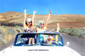 Fast party girls ride three attractive pretty riding in a classic convertible with the top down on a desolate country road smoking Royalty Free Stock Photos
