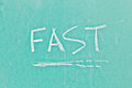 Fast sign written in white chalk on a green board Stock Images
