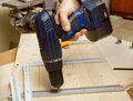 Fastening with an electric screwdriver furniture parts in production of Stock Photos