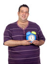 Fat man with a blue alarm clock Stock Photo