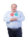 Fat Man in a Blue Shirt, Eating a Lollipop Royalty Free Stock Photography