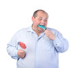 Fat Man in a Blue Shirt, Eating a Lollipop Royalty Free Stock Photo