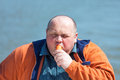 Fat man eating a carrot on background of water Royalty Free Stock Photo