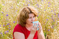 Fat woman with allergic rhinitis in meadow the Royalty Free Stock Image