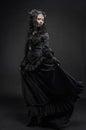 Fatal woman in vintage black dress posing on dark background Stock Photo