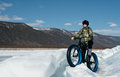 Fatbike x fat bike or fat tire bike x also called cycling on large wheels extreme girl riding a on snow melted ice the lake Royalty Free Stock Photo