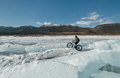 Fatbike x fat bike or fat tire bike x also called cycling on large wheels extreme girl riding a on snow melted ice the lake Stock Image