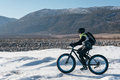 Fatbike x fat bike or fat tire bike x also called cycling on large wheels teen rides a bicycle through the snow mountains in the Stock Photo