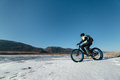 Fatbike x fat bike or fat tire bike x also called cycling on large wheels teen rides a bicycle through the snow mountains in the Royalty Free Stock Images