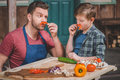 Father in apron and cute little son having fun with pepper moustaches Royalty Free Stock Photo