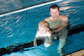 Father and baby boy swimming in a swimming pool Royalty Free Stock Photography