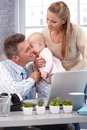Father and baby daughter kissing businessman sitting at desk working with laptop computer wife holding for kiss Stock Image