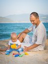 Father and baby are playing beach toys Stock Image