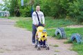 Father and baby son age of months walking with carriage Royalty Free Stock Images