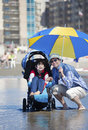 Father at beach with disabled son in wheelchair holding umbrella over the Royalty Free Stock Photo