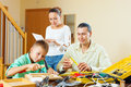 Father and boy spend their free time with working tools at home happy women helping them Royalty Free Stock Images