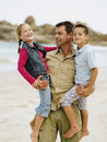 Father carrying his children on the beach Stock Photo