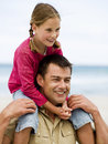 A father carrying his daughter on his shoulders at the beach Royalty Free Stock Image