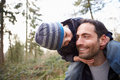 Father carrying son on shoulders during countryside walk Stock Photo