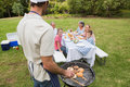Father in chefs hat and apron cooking barbecue for his family sitting at picnic table Stock Photos