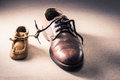 Father and child shoes still life photography on grunge background tie the shoestring together in vintage color tone love Stock Images