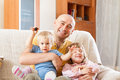 Father with children dad and two daughters on sofa Royalty Free Stock Photos