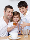 Father and children eating biscuits with milk Royalty Free Stock Images