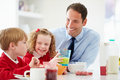 Father and children having breakfast in kitchen together eating cereal drinking orange juice Royalty Free Stock Photos
