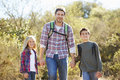 Father and children hiking in countryside wearing backpacks Stock Photos