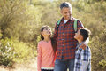 Father and children hiking in countryside wearing backpacks Royalty Free Stock Photo