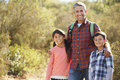 Father and children hiking in countryside wearing backpacks Stock Photography