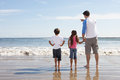 Father and children looking to sea from beach rear view of Stock Image