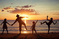 Father and children playing on the beach at the sunset time. Royalty Free Stock Photo
