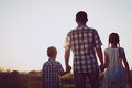 Father and children playing in the park at the sunset time. Royalty Free Stock Photo