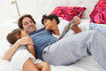 Father and children relaxing in bed together reading Royalty Free Stock Images