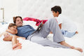 Father and children relaxing in bed together smiling Royalty Free Stock Image