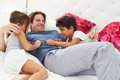Father and children relaxing in bed together smiling to each other Stock Photo
