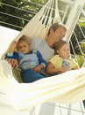 Father and children relaxing in hammock on balcony sleeping tilt Stock Image