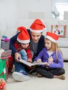 Father and children in santa hats reading book full length of at home Royalty Free Stock Images