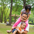 Father and children southeast asian family having fun at green outdoor park beautiful muslim family playing together Stock Photo