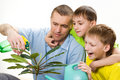 Father and children watering flower Stock Image
