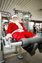Father christmas doing exercises in gym before delivering presents Stock Images