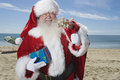 Father Christmas Stands With His Sack On Beach Royalty Free Stock Images