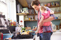 Father Cooking Meal Whilst Holding Daughter In Kitchen Royalty Free Stock Photo