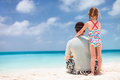 Father and daughter at beach back view of enjoying vacation Stock Photo