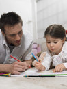 Father and daughter coloring book on floor together at home Royalty Free Stock Photography